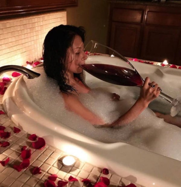 funny photos of woman drinking giant glass of wine in bubble bath