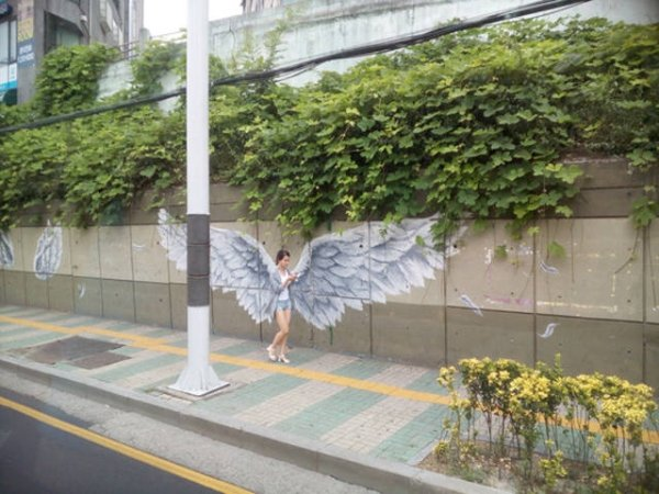 funny photo of perfectly timed shot of girl walking in front of wings painted on a wall