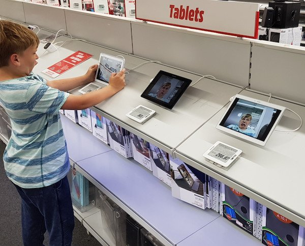 funny pic of kid taking selfies and putting them on every tablet in store