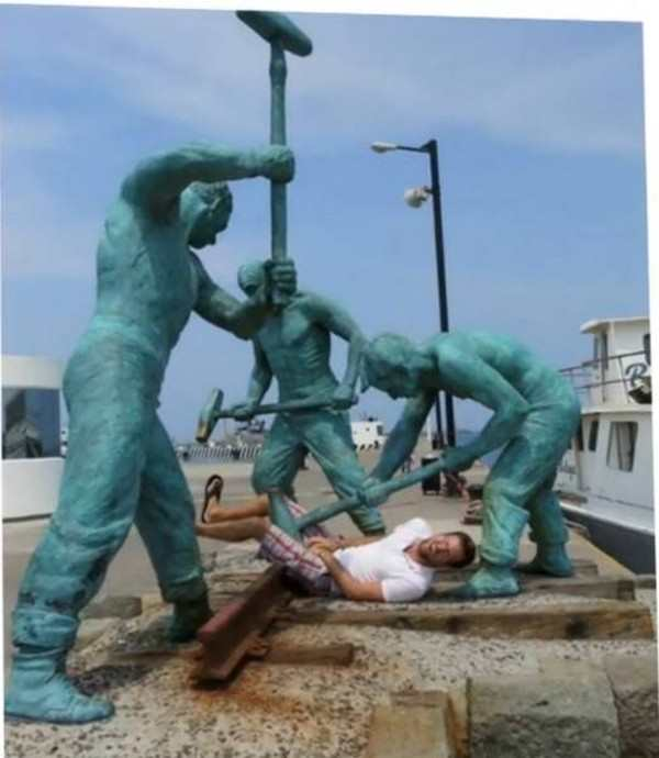silly picture of guy pretending statues are smashing his balls