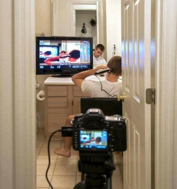 funny picture of guy giving himself a haircut using a camera and monitors