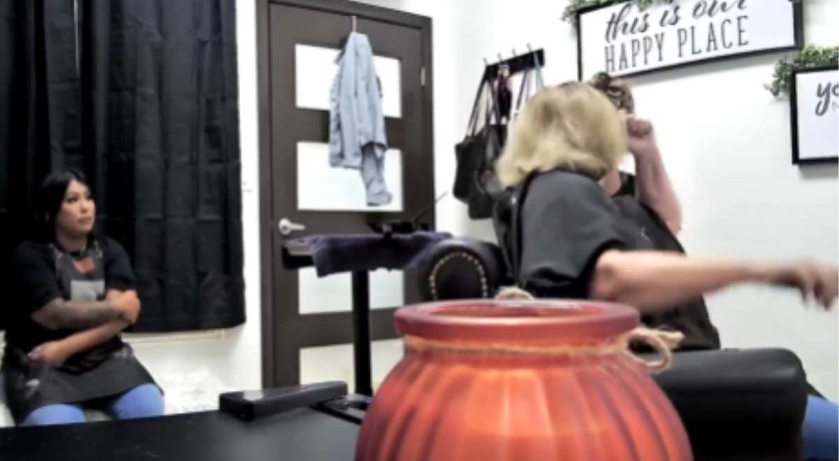 woman trying to hit a hairstylist